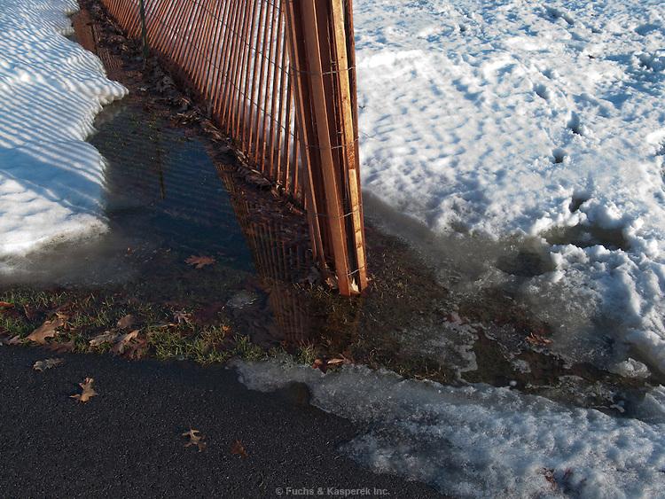 A late-winter thaw creates a slushy mess near a snow fence.