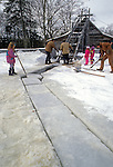 Kids and adults working at the annual ice harvest at the Thompson Ice House, Bristol, Maine, USA