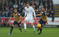 Gylfi Sigurdsson of Swansea City in action against Santi Cazorla and Francis Coquelin of Arsenal during the Barclays Premier League match between Swansea City and Arsenal played at The Liberty Stadium, Swansea on October 31st 2015