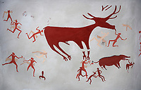 Close up of a recontructed fresco of an original found at Catalhoyuk. The men are hunting a deer and pulling on its tounge to disable it. The hunters are believed by scholors to be wearing leopard skin costumes, Reconstructed houses, Painted by Mutlu Gundiler. 7500 BC to 5700 BC, Catalyhoyuk Archaeological Site, Çumra, Konya, Turkey