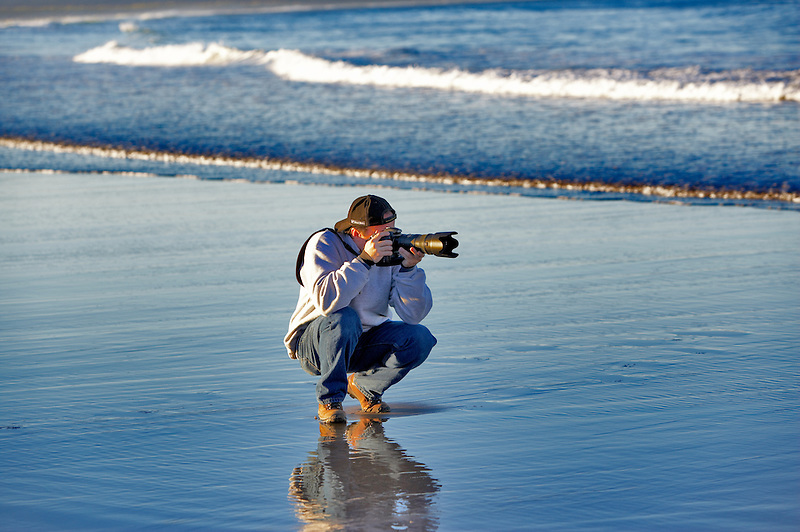 Photographer taking pictures at Cape Kiwanda. Oregon