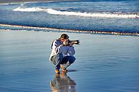 Photographer taking pictures at Cape Kiwanda. Oregon