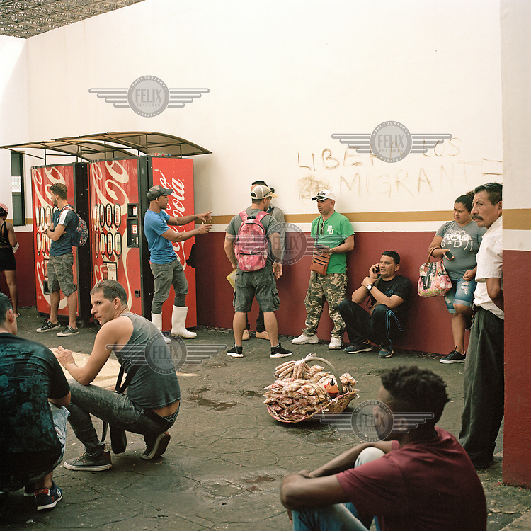Nationals from Haiti, Cuba and various central American countries wait at the gates of migratory station 'Siglo XXI'.