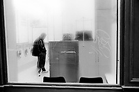 France. Ile-de-france Department. Paris. Marais district. Condensation on window panes of a laundromat. A man, both hands in his pant's pockets, stands alone in front of a washing machine. Writings on the steamed window. A laundromat is a self-service laundry and a facility where clothes are washed and dried. 24.02.05 © 2005 Didier Ruef