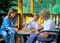 3 generations of family playing a board game outdoors