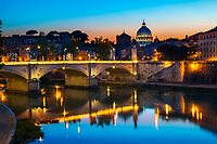 Colorful sunset on the famous, lit-up St. Peter's Basilica and St. Angelo Bridge reflecting on the Tiber River, Vatican, Rome Italy, Southern Europe