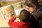 Preschool 3-4 year olds teacher in training or therapist working with boy reading book horizontal