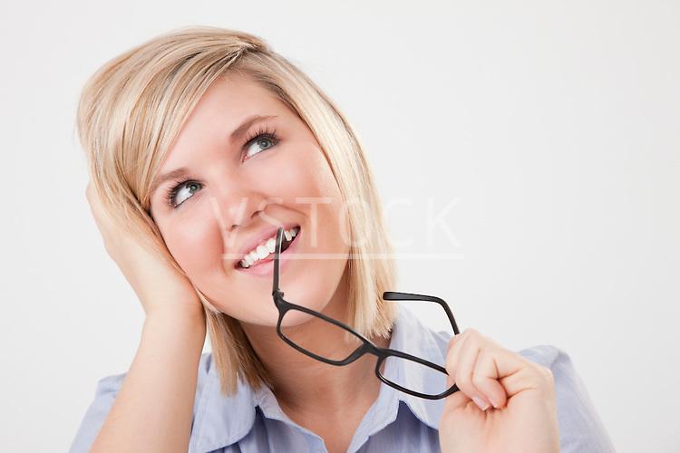 USA, Illinois, Metamora, studio portrait of young woman biting eyeglasses