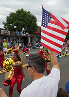 Man waving American Flag, Independence Day Parade 2016, Burien, Washington, USA.