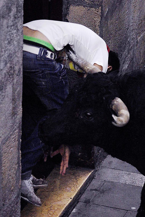 Participants run ahead of fighting bulls during a San Fermin bullrun in Pamplona..SAN FERMIN BULL RUN IRUÑA BASQUE COUNTRY ANDER GILLENEA
