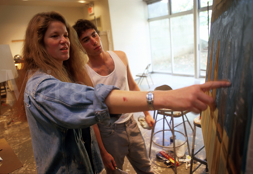 A college professor critiques a student's artwork in a college art studio. Wesleyan University.