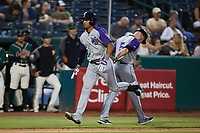 Luis Curbelo (16) of the Winston-Salem Dash slaps hands with third base coach Ryan Newman (5) after hitting a home run against the Greensboro Grasshoppers at First National Bank Field on June 3, 2021 in Greensboro, North Carolina. (Brian Westerholt/Four Seam Images)