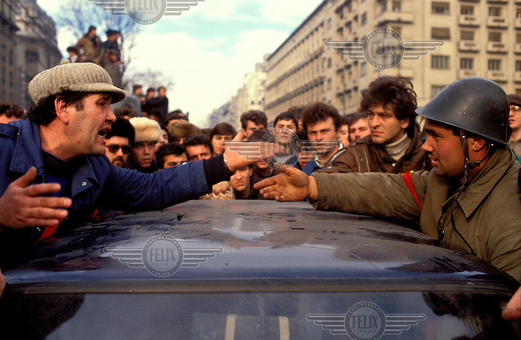 © Paul Lowe / Panos Pictures..Bucharest, Romania. .Revolution, 22nd-25th December 1989...A crowd gathers as a soldier arrests a suspected member of the Securitate...The Romanian popular revolt and coup of December 1989 represented a decisive moment in the collapse of communism in Eastern Europe. An uprising which had begun a week earlier in the town of Timisoara spread to the capital city, Bucharest, with demonstrations leading to violent clashes in the streets. Nicolae Ceaucescu, President since 1974, lost the support of the army, who sided with ordinary civilians in street battles against the feared Securitate secret police force. As Ceaucescu and his wife Elena attempted to flee the country, they were captured, tried and executed. Their dead bodies were exhibited on television on Christmas Day. In just a few dramatic days, the country had rejected the communist system which had ruled since the Second World War. The slow and difficult transition to capitalism began.