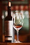 Wine Glass and Wine Bottle in Wine Shop, mirror background, warm tones, open bottle.