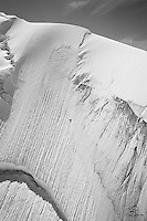 Wind erosion and shifting tectonic plates create dynamic textures on the face of a glacier in the Tordrillo Mountains, Alaska Range. Matanuska Susitna, Alaska. Shot from helicopter.