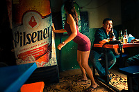 A Salvadoran sex worker seduces a man while dancing at his table in a street sex bar in San Salvador, El Salvador, 30 November 2018. Although prostitution is not legal in El Salvador, dozens of street sex workers, wearing provocative miniskirts, hang out in the dirty streets close to the capital's historic center. Sex workers of all ages are seen on the streets but a significant part of them are single mothers abandoned by their male partners. Due to the absence of state social programs, they often seek solutions to their economic problems in sex work. The environment of street sex business is strongly competitive and dangerous, closely tied to the criminal networks (street gangs) that demand extortion payments. Therefore, sex workers employ any tool at their disposal to struggle hard, either with their fellow workers, with violent clients or with gang members who operate in the harsh world of street prostitution.