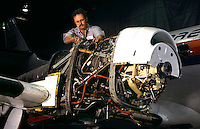 A worker assembling electrical components of a turbo-prop engine
