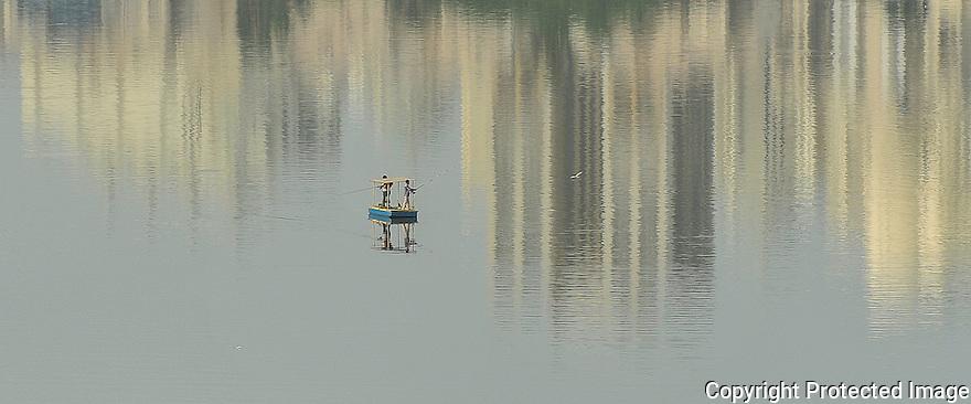 Men fishing in Powai lake in Mumbai