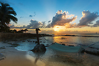 Colorful sunset with sunrays through the clouds and a hammock, on a white sand beach above the clear water, Cozumel Island Caribbean Sea, Mexico