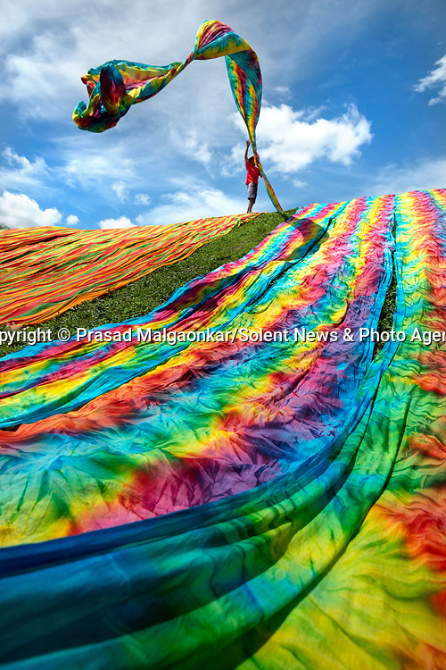 Workers dry huge sheets of coloured cotton by throwing them down a grassy hillside.  The fabric is dyed with bright colours before intricate patterns of dots and lines are made on the material.<br /> <br /> These beautiful photographs were captured in the city of Surakarta, a historic city on the Indonesian island of Java.  SEE OUR COPY FOR DETAILS.<br /> <br /> Please byline: Prasad Malgaonkar/Solent News<br /> <br /> © Prasad Malgaonkar/Solent News & Photo Agency<br /> UK +44 (0) 2380 458800