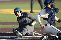 Michigan State outfielder Bryce Kelley (17) slides at home against the Michigan Wolverines on March 21, 2021 in NCAA baseball action at Ray Fisher Stadium in Ann Arbor, Michigan. Michigan scored 8 runs in the bottom of the ninth inning to defeat the Spartans 8-7. (Andrew Woolley/Four Seam Images)