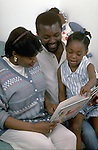 pregnant mother reads with father and young daughter