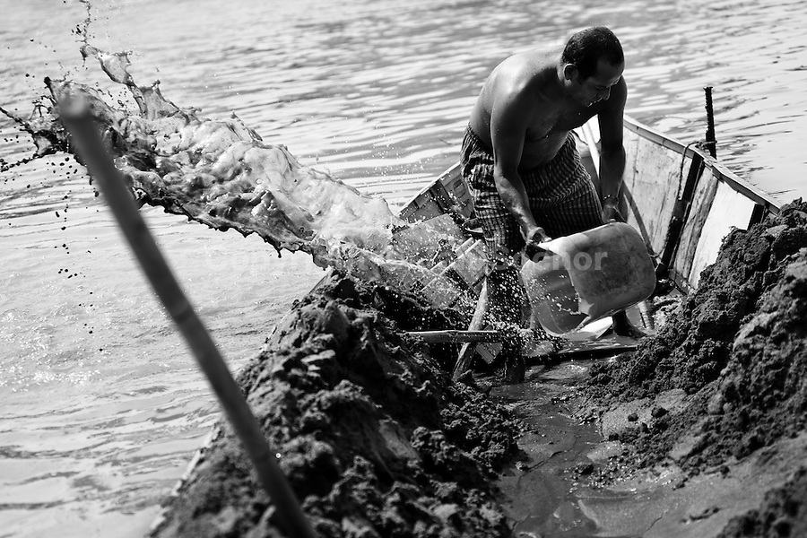 A Colombian sand miner bails the water out of the boat anchored in the middle of the river La Vieja in Cartago, Colombia, 14 April 2013. Artisanal (unmechanised) sand mining is an ancient mining technique used to obtain sand for construction purposes. Depending on the natural conditions (strength of the stream, depth of the river etc.), together with the sand miners' physical condition, the material is extracted in metal buckets, either by standing on the river bottom and searching for sand by feet, or, diving up to 3-5 meters deep using a wooden plank with steps. In spite of the physically demanding work, a sand miner's daily salary does not exceed 15-20 US dollars. However, the sand miners are very proud of their profession, valuing their work freedom above all, and usually, as long as their health and strength permit, they keep facing the river stream.