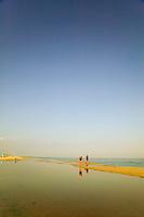 Couple walking along a deserted beach.