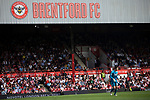 Home supporters in the Braemar Road stand watching the first-half action as Brentford hosted Leeds United in an EFL Championship match at Griffin Park. Formed in 1889, Brentford have played their home games at Griffin Park since 1904, but are moving to a new purpose-built stadium nearby. The home team won this match by 2-0 watched by a crowd of 11,580.
