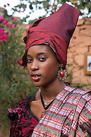 Goree Resident Dressed as a Signare, Senegalese wives of 18th-19th-century French merchants.  Signare comes from the Portuguese senhora.  Though signares reached their apogee of social status in the late 18th century, the practice of taking local wives to facilitate trading relationships probably dates back to the arrival of the Portuguese on Goree in 1444.