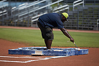 A member of the grounds crew taps a box that drops chalk onto the field to draw the batter's box prior to the Appalachian League game between the Bristol Pirates and the Danville Braves at American Legion Post 325 Field on July 1, 2018 in Danville, Virginia. The Braves defeated the Pirates 3-2 in 10 innings. (Brian Westerholt/Four Seam Images)