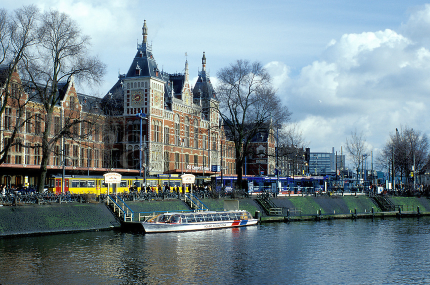 Amsterdam, The Netherlands, Holland, Europe, Tour boat along a canal in front of Central Station in Amsterdam.