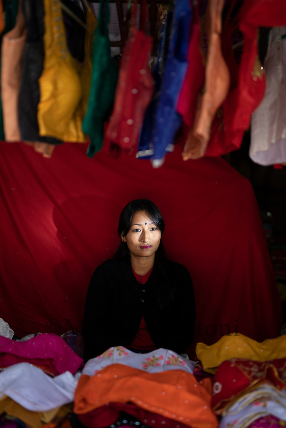 India - Manipur - Imphal - Akoijam Kalpana Chanu, 34 years old. From Tera Yengkhom Leirak, in Imphal. They work under a woman who owns the stall, they are paid daily. She gets 300 rupees per day. She has been working in this for the past ten years. Earlier it was mandatory that only married women were in the market, but now, in order to support the financial situation for a family, they want to earn their pocket money and not rely financially on the family. She must been the very first  unmarried woman working in the market. There are some other, but she was the first one. She wish to have her personal stall in the future, but no one is willing to sell her stall, plus she hasn't saved that amount of money, because it's gonna be in the lakhs (the price for a stall). She would like to stay here in the market, not in a shop. Because they went through the hard beginnings, they gained the trust of the other women…