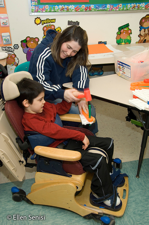 MR / Albany, NY.Langan School at Center for Disability Services .Ungraded private school which serves individuals with multiple disabilities.A mother visiting the classroom helps her son grasp and pound with a plastic hammer from a play tool set. Boy: 8, cerebral palsy, spastic quadriplegic, nonverbal with expressive and receptive language delays.MR: Hac2, Ble1.© Ellen B. Senisi