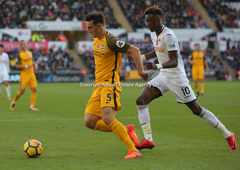 (L-R) Lewis Dunk of Brighton is chased by Tammy Abraham of Swansea City during the Premier League match between Swansea City and Brighton and Hove Albion at The Liberty Stadium, Swansea, Wales, UK. Saturday 04 November 2017