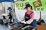 Vendors prepare freshly roasted pieces of seaweed wrap (nori or kim)