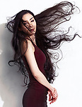 Portrait of a Japanese woman in burgundy dress with long flying in the wind black hair on white background Image © MaximImages, License at https://www.maximimages.com