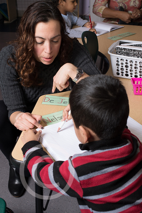 Education Preschool Childcare 3-4 year olds SEIT working with boy in classroom on writing name and motor skills