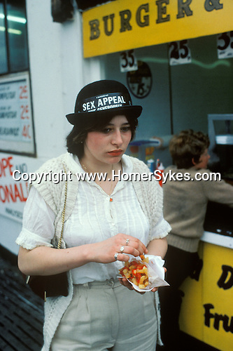Blackpool, Lancashire. 1980's<br /> In her 'Sex Appeal Give Generously' novelty bowler hat, a rather depressed young teen eats a bag of chips covered in tomato ketchup.