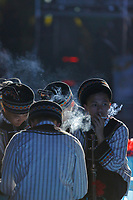Youths of the ethnic Bouyei Tribe smoke at the city centre of Wangmo County in China's southwestern Guizhou Province, April 2019.