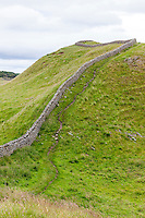 Northumberland, England, UK.  Hadrian's wall and Footpath going upwards toward Sewingshields Crags.