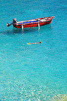 A red wooden motorboat moored in a quiet cove adds a splash of colour to the azure blue water