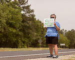 May 5, 2018. Fayetteville, North Carolina.<br /> <br /> Debra Grabauskas holds a sign about the GenX pollution of the Cape Fear River on Hwy. 87 just outside the Chemours plant which has been dumping GenX unregulated into the river for years. <br /> <br /> The Chemours Company, a spin off from DuPont, manufactures many chemicals at its plant in Fayetteville, NC. One of these, commonly referred to as GenX, is part of the process of teflon manufacturing. Chemours has been accused of dumping large quantities of GenX into the Cape Fear River and polluting the water supply of city's down river and allowing GenX to leak into local aquifers.