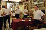 Venice Italy 2009. Interior restaurant waiters sampling dinner guests wine.