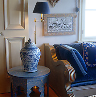 A carved and hand-painted wooden banquette is upholstered with blue velvet cushions in the blue sitting room