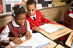 K-8 Parochial School Bronx New York Grade 3 mathematics lesson on measurement using rulers boy and girl working ad desks horizontal