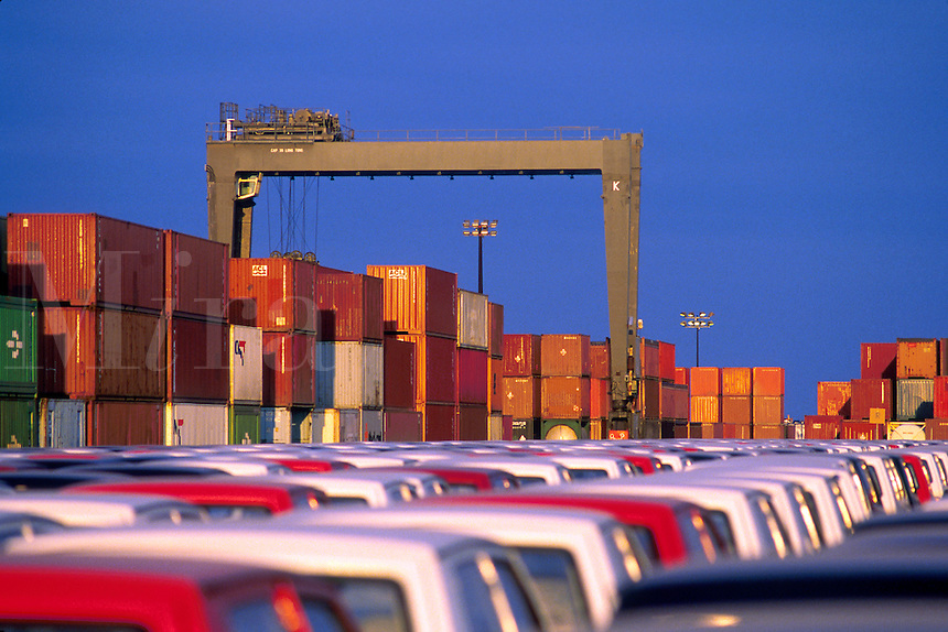 A lot of recently unloaded import cars, crane reading 'Port of Houston'and cargo containers. Houston, Texas.