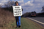 Village Pub food. Sandwich board man walking along the A 303 road in Wiltshire England 1990s UK<br /> Brian Harwood advertising local pub next on the left, the pub is having financial difficulty.