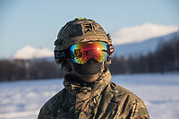 Ground crew dressed for receiving a Royal Navy helicopter n the Arctic. British Merlin helicopter practice in the Arctic, picking up loads in the terrain near Bardufoss, Norway. <br /> In 2019 the Arctic exercise Clockwork passed 50 years of training in Norway, and now has a permanent base within the Norwegian Air Force base at Bardufoss. <br /> <br /> 845 Naval Air Squadron is a squadron of the Royal Navy's Fleet Air Arm. Part of the Commando Helicopter Force, it is a specialist amphibious unit operating the Commando Merlin Mk3 helicopter and provides troop transport and load lifting support to 3 Commando Brigade Royal Marines.<br /> <br /> ©Fredrik Naumann/Felix Features