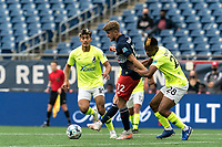FOXBOROUGH, MA - MAY 12: Justin Rennicks #12 of New England Revolution II passes the ball as Illal Osumanu #28 of Union Omaha pressures during a game between Union Omaha and New England Revolution II at Gillette Stadium on May 12, 2021 in Foxborough, Massachusetts.